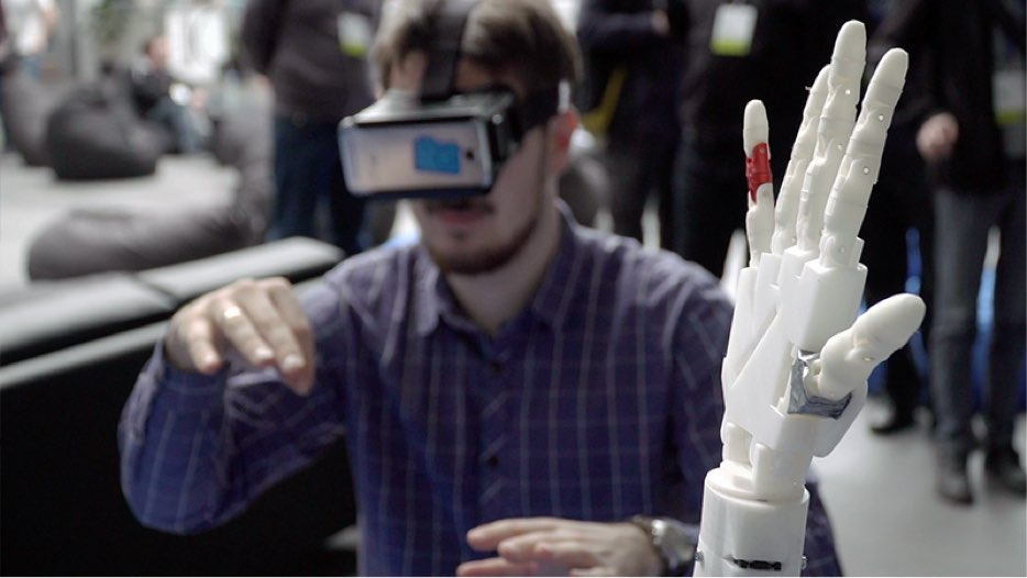 Photo of a man using a VR headset to control a robotic hand.